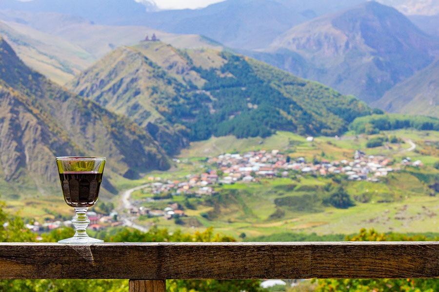 A glass of Georgian Wine on the background of the Georgian village and Kazbeg mountain near the village of Stepantsminda on the Georgian military road. Kazbegi Georgia